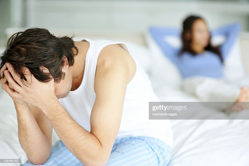 Frustrated man sitting on edge of bed : Stock Photo