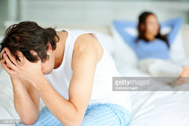 Frustrated man sitting on edge of bed
