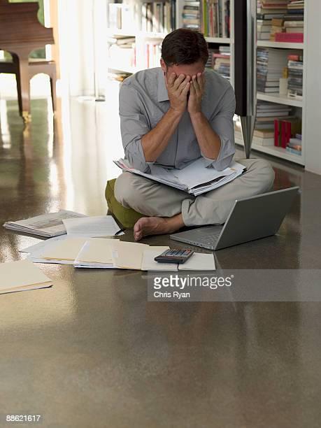 frustrado hombre sentado en el suelo con papeleo y computadora portátil - mid adult men fotografías e imágenes de stock