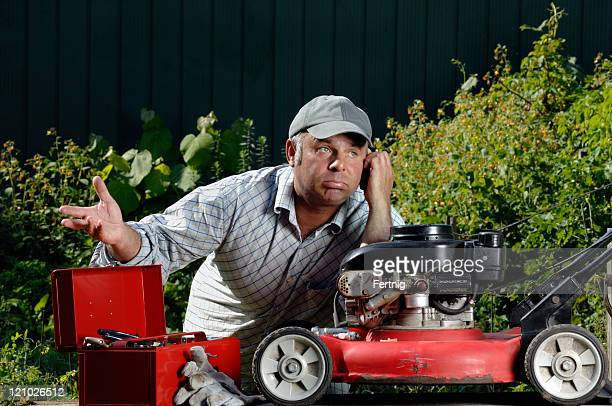 Frustrated man trying to fixing a lawnmower on the phone
