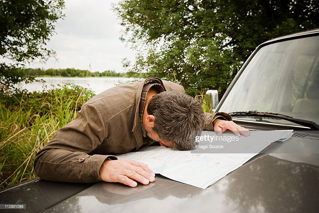 Frustrated man with head on map on car hood : Stock Photo