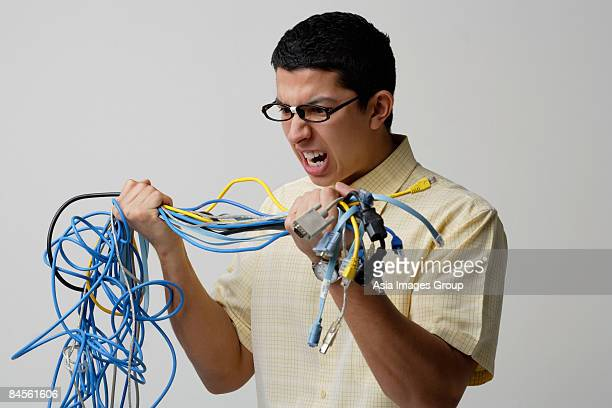Frustrated man with tangled wires