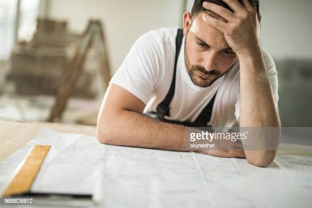 frustrated manual worker having problems with blueprints at construction site. - disappointment stock pictures, royalty-free photos & images