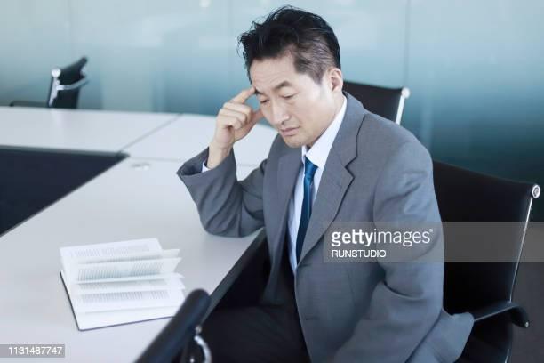 frustrated mature businessman at desk - 中年の男性一人 ストックフォトと画像