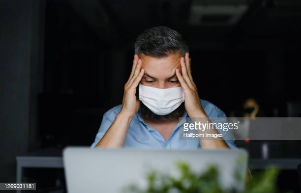 frustrated mature man with face mask sitting indoors in office, working. - stress coronavirus stock pictures, royalty-free photos & images