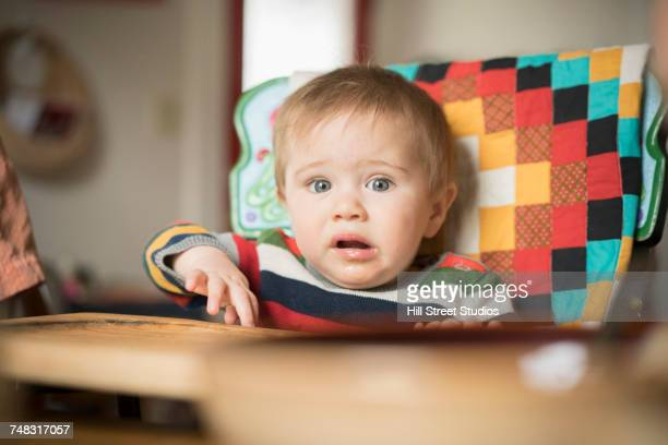 frustrated mixed race baby boy sitting in high chair - tensed idaho stock photos and pictures
