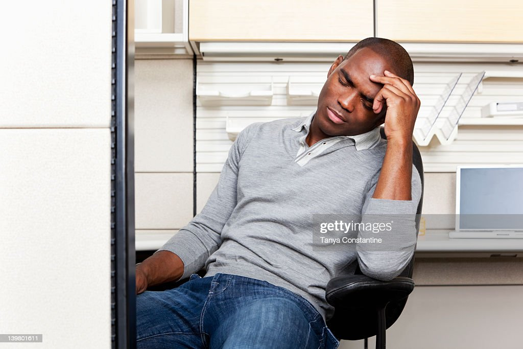 Frustrated mixed race businessman sitting in office cubicle : Stock Photo