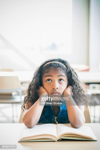 frustrated mixed race girl reading book in library - tensed idaho stock photos and pictures