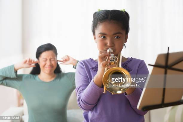 Frustrated mixed race mother listening to daughter practicing trumpet