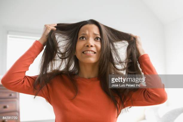 Frustrated mixed race woman pulling her hair