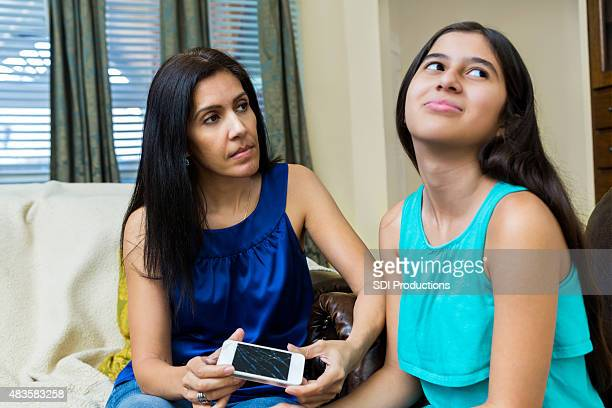 Frustrated mom holding broken smart phone while talking to preteen
