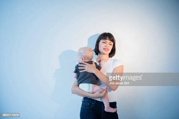 frustrated mother holding baby son - postpartum depression stock pictures, royalty-free photos & images