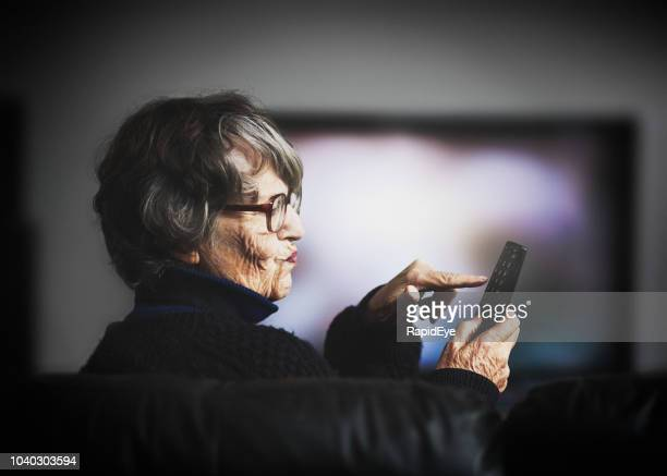 frustrated old woman attempting to use tv remote - ineptitude stock pictures, royalty-free photos & images