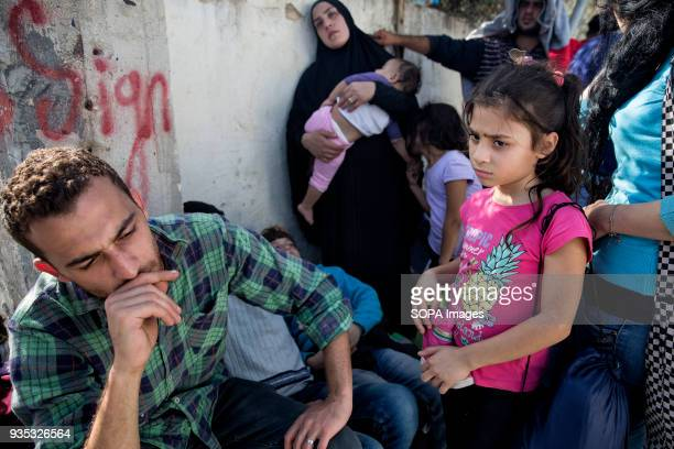 A frustrated PalestinianSyrian family waits under hot sun outside Moria Camp for asylumseekers and migrants after being told they should go to...
