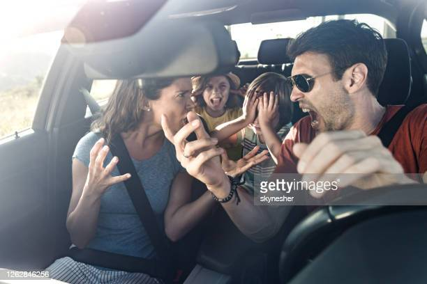 frustrated parents arguing during trip by a car. - fighting stock pictures, royalty-free photos & images