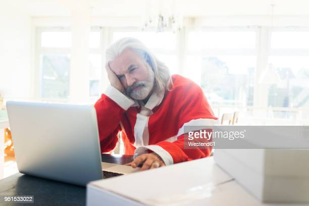 frustrated santa using laptop at home - pere noel humour photos et images de collection