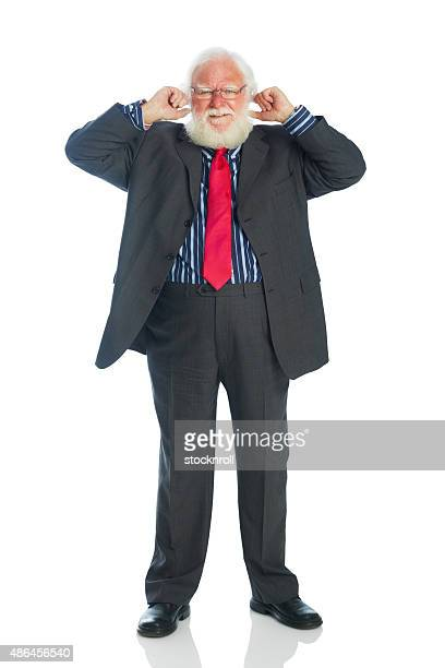 Frustrated senior businessman with fingers in ears