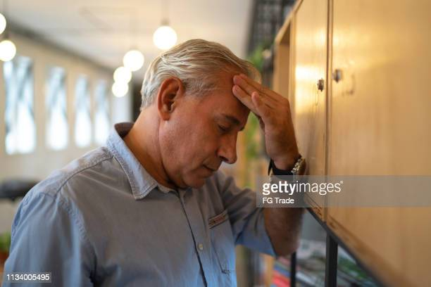 frustrated senior businessman with headache at work - chronic illness stock photos and pictures