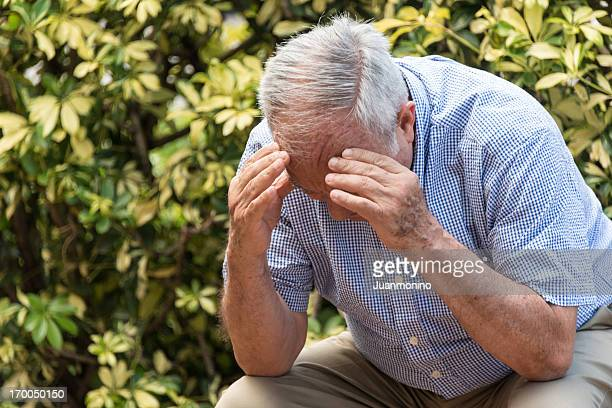 Frustrated senior man with head in his hands