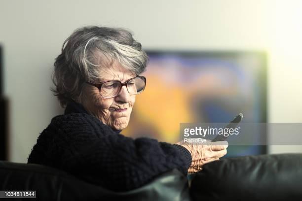 donna anziana frustrata che spinge cupamente i controlli sul telecomando della tv - controllato a distanza foto e immagini stock