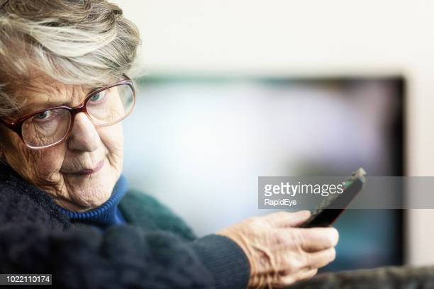 frustrated senior woman turns to camera from tv - disappointment stock pictures, royalty-free photos & images
