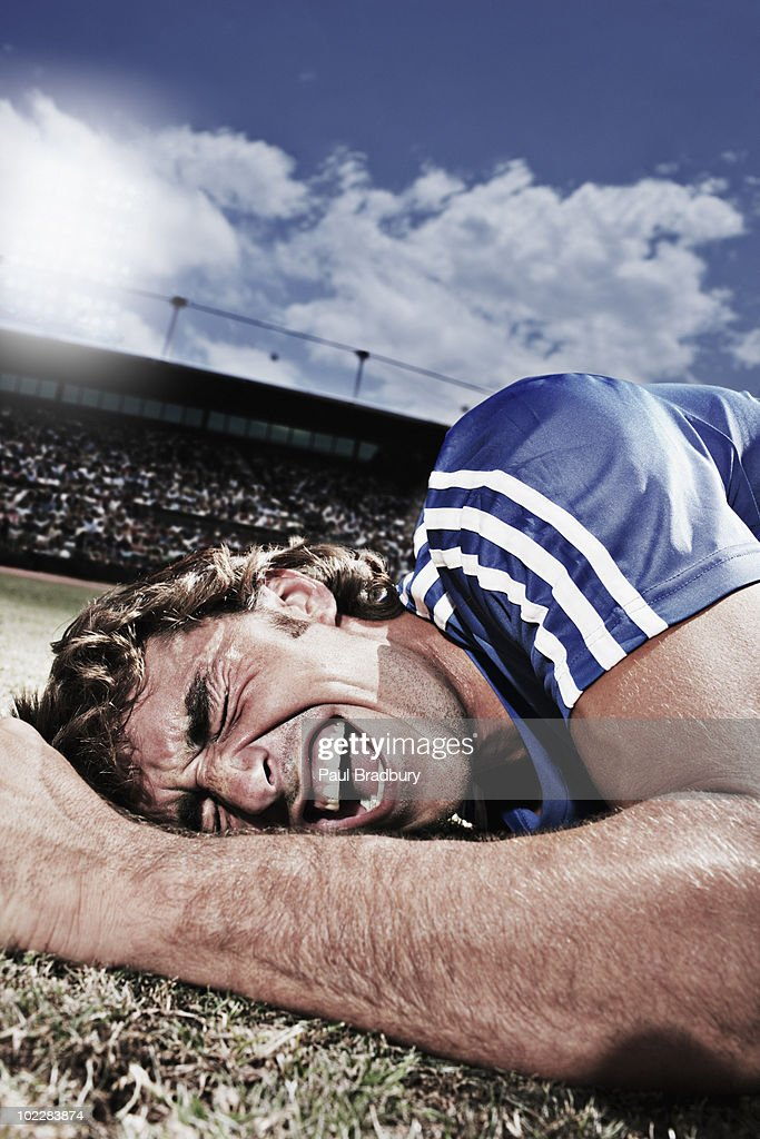 Frustrated soccer player laying on ground : Stock Photo