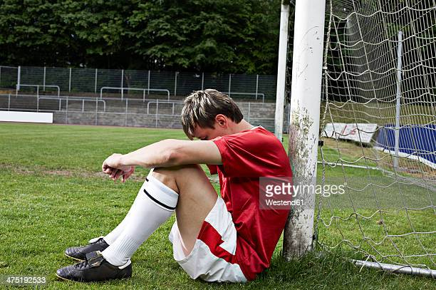 frustrated soccer player on field - niederlage stock-fotos und bilder
