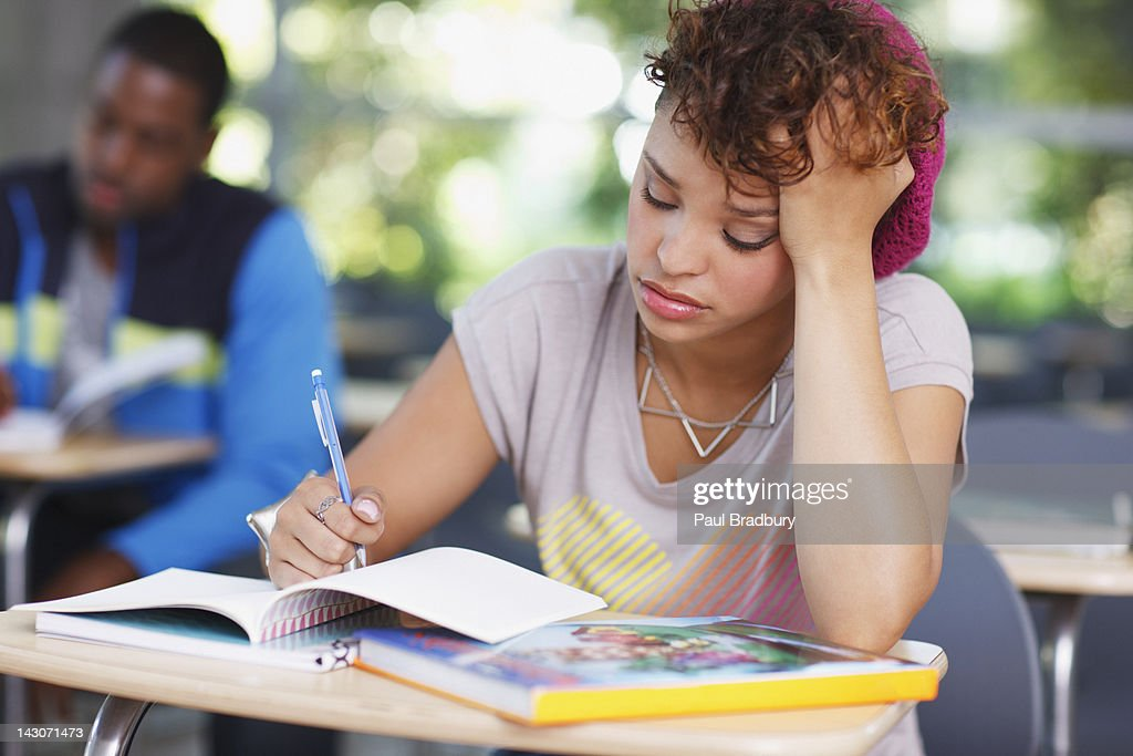 Frustrated student at work in classroom : Stock Photo