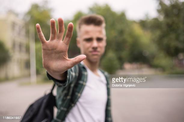 frustrated teenager putting his hand - anti bullying symbols stock pictures, royalty-free photos & images