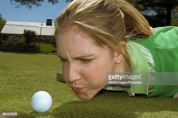Frustrated woman blowing on golf ball, close-up