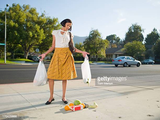 Frustrated woman dropping groceries on sidewalk