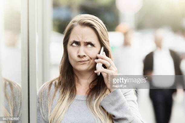 Frustrated woman in street listening on phone rolls her eyes