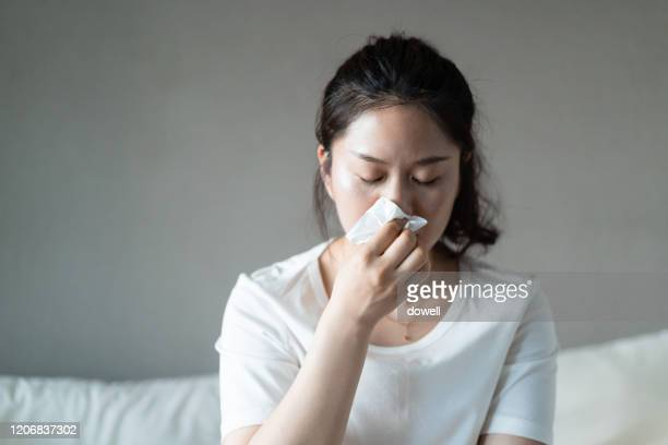 frustrated  woman using a tissue to sneeze - blowing nose stock pictures, royalty-free photos & images
