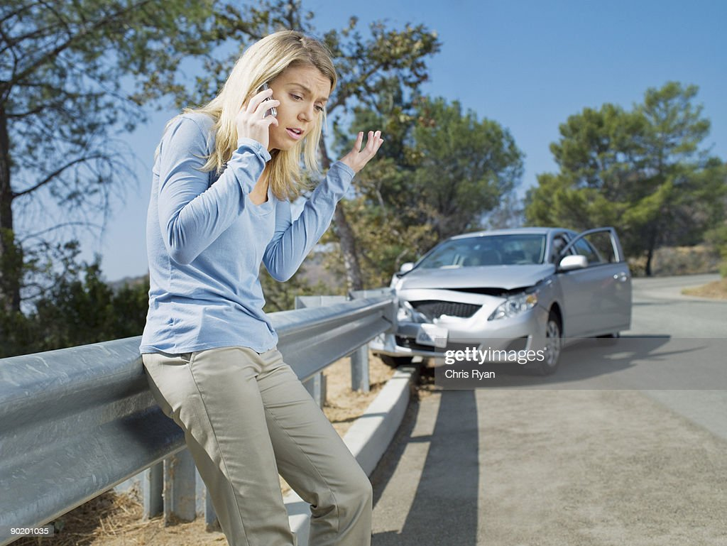 Frustrated woman using cell phone next to car wrecked on guardrail : Stock Photo