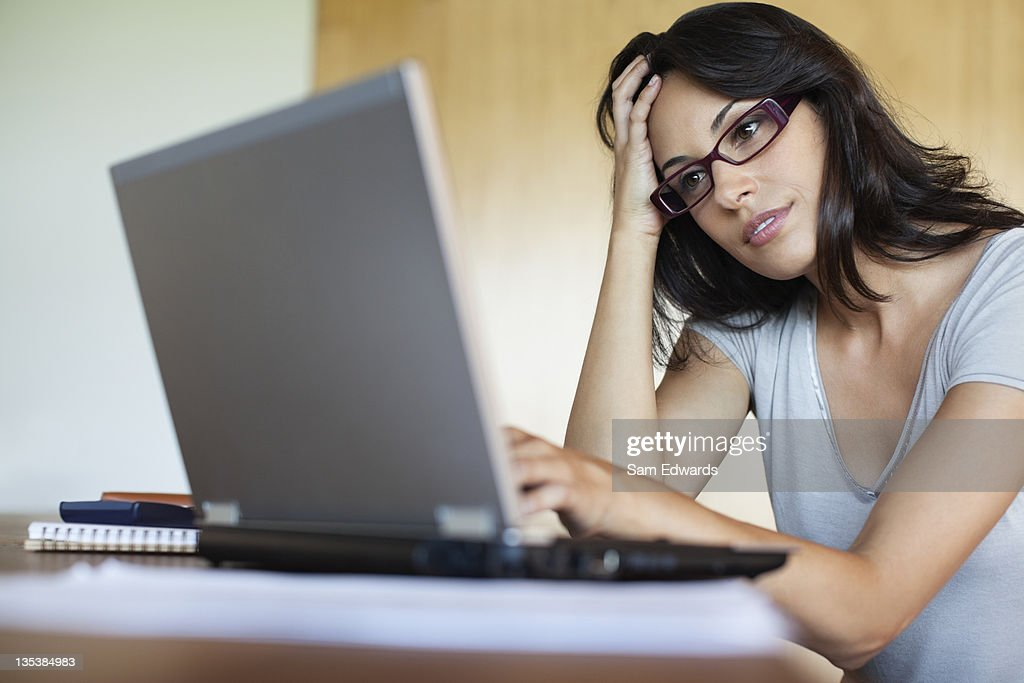 Frustrated woman using laptop : Stock Photo