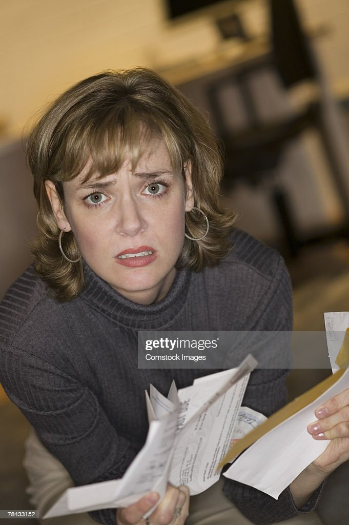 Frustrated woman with bills : Stockfoto