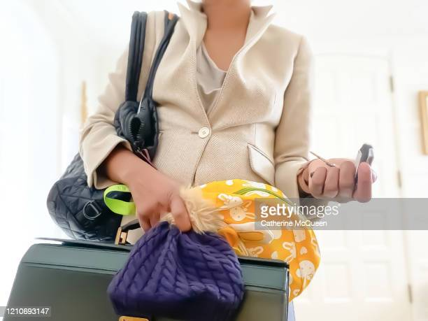 frustrated working mother shrugs as she rushes to leave home for work - woman hurry stockfoto's en -beelden