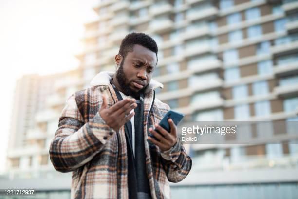 gefrustreerde jonge mens die telefoon gebruikt. - frustratie stockfoto's en -beelden