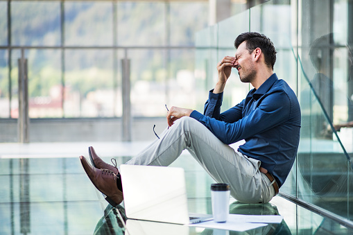 Frustrated young man with laptop sitting on the floor in the modern building, holding his head. - gettyimageskorea