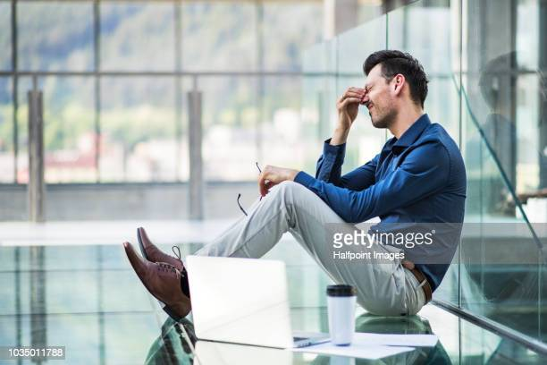 frustrated young man with laptop sitting on the floor in the modern building, holding his head. - teleurstelling stockfoto's en -beelden