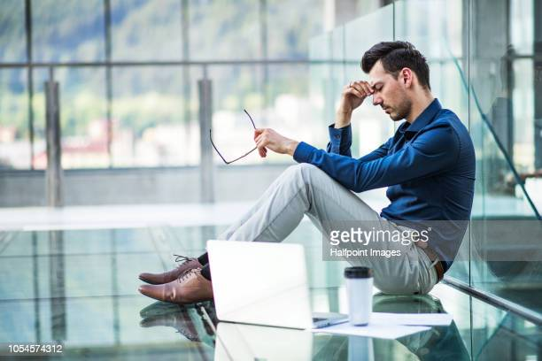 Frustrated young man with laptop sitting on the floor in the modern building, holding his head.