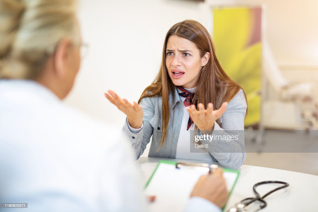 Frustrated young woman talking with her doctor. : Stock Photo