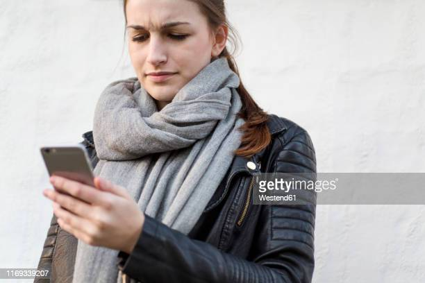 frustrated young woman using her smartphone - fury stock pictures, royalty-free photos & images