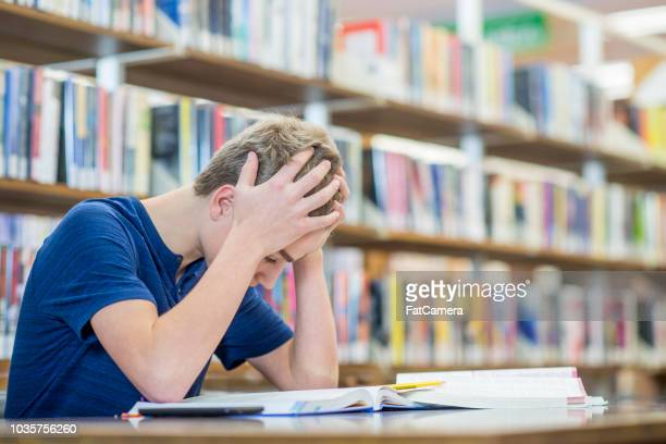 frustration studying in the high school library - struggle stock pictures, royalty-free photos & images