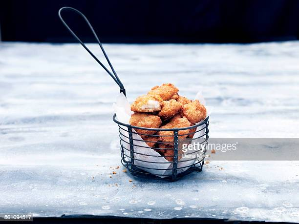 Frying basket full of breaded Scottish wholetail scampi