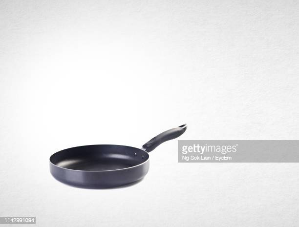 frying pan against white background - frying pan stock pictures, royalty-free photos & images