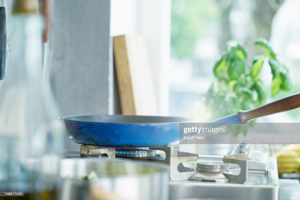 Frying pan on lit hob : Stock Photo