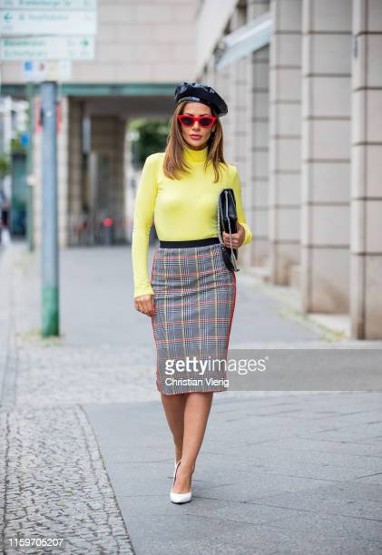 Füsun Lindner is seen wearing total look Marc Cain black white two tone heels neon turtleneck plaid skirt bag beret red sunglasses during Mercedes...