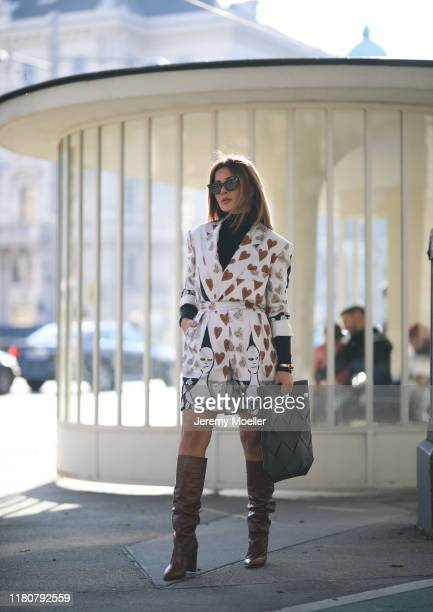 Füsun Lindner wearing a Max Mara short and blazer, Paris Texas overknees, Bottega Veneta bag, Wolford turtleneck and Celine bangle on October 12,...