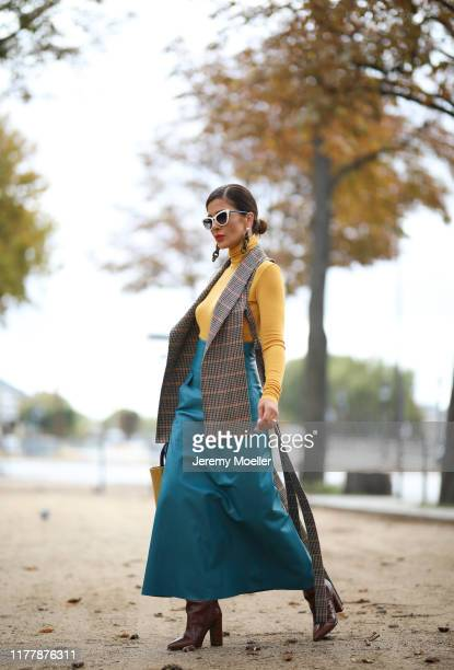 Füsun Lindner wearing a vest and skirt by Nobi Talai bag from by Far Paris Texas boots and a Prada sunglasse on September 27 2019 in Paris France